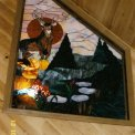 Big Buck Trapezoid Window - An interior window is the showpiece in the loft of a lovely Wisconsin Country Home.  The big buck deer is the center of attraction and showing off his beauty among all his favorite surroundings of pine trees, a trickling stream with flat rocks, and wild flowers.